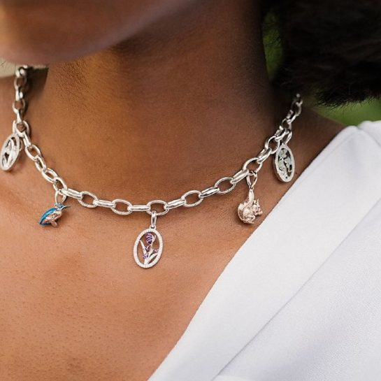 Model wearing white top and Links of London sterling silver chain necklace with kingfisher and red squirrel charm.