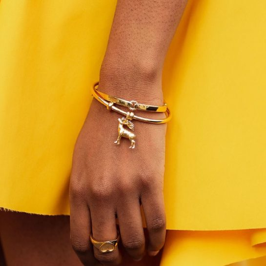 Model wearing yellow dress and Links of London Wildlife Red Deer Stag Charm on gold vermeil bangle.