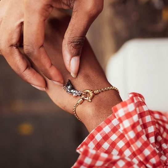 Model wearing red and white gingham top and Links of London gold vermeil bracelet with Atlantic puffin charm.