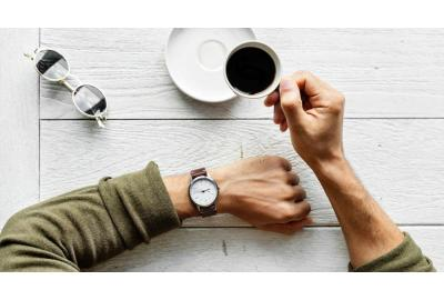 man wearing watch and drinking coffee