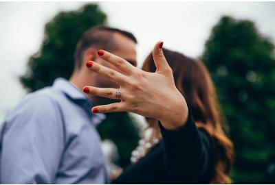 couple kissing with hand in focus showing engagement ring