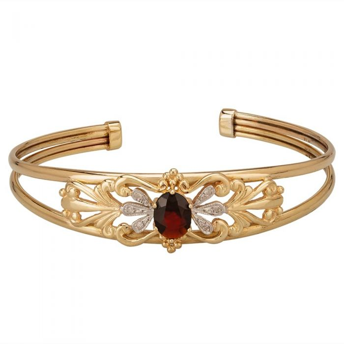 yellow gold torque bangle with ruby centre stone surrounded by diamonds