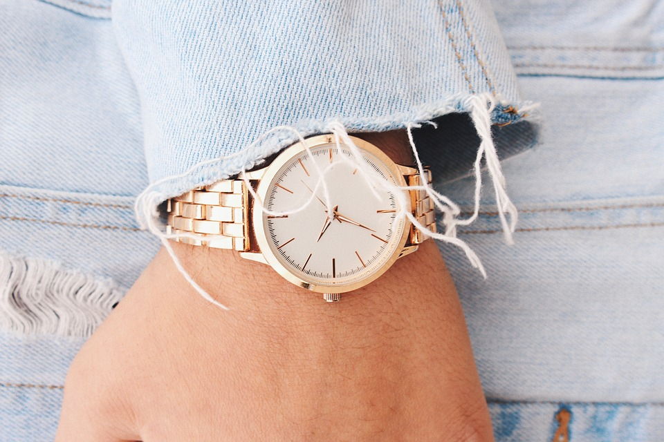 woman wearing gold bracelet watch