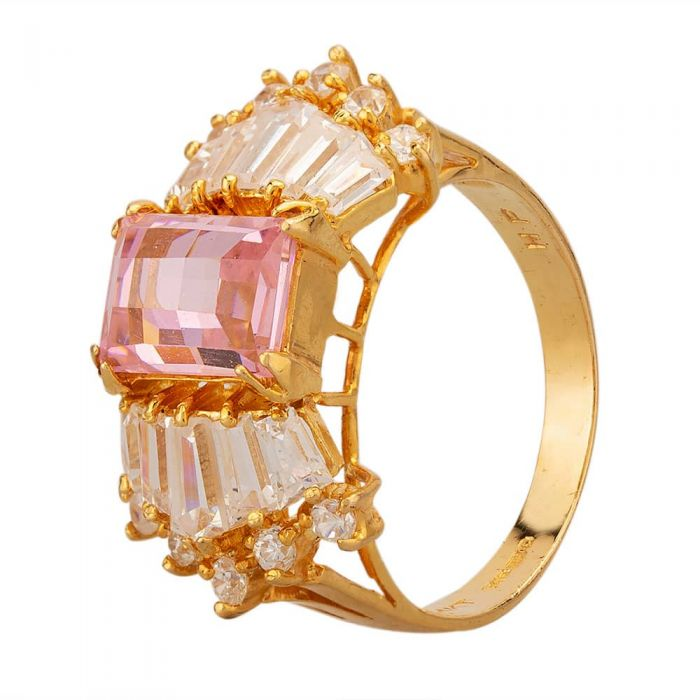 a 14 carat yellow gold ring with a pink cubic zirconia stone, flanked with baguette-cut and round white stones